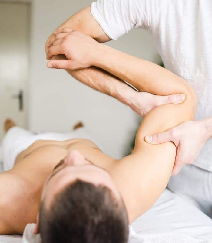 Young man male athlete having sport massage at spa or home by professional therapist relax body recovery healing injury shoulder chiropractics arm