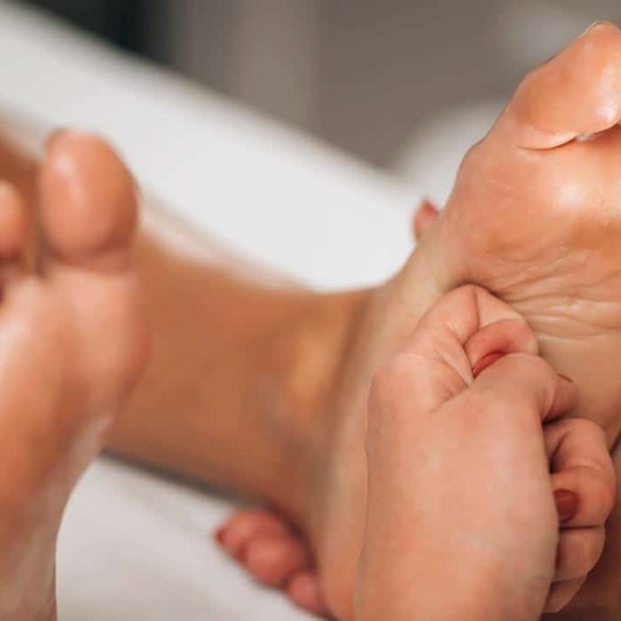 Acupressure meridian point foot treatment. Practitioner applying pressure to meridian points on Female Foot