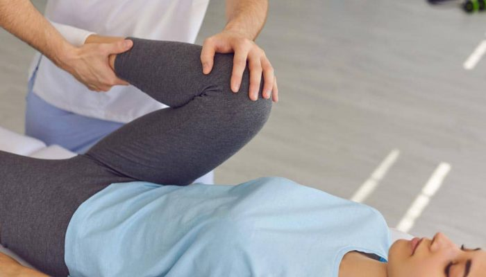 Young woman patient lying and getting procedure of knee and leg joints from chiropractor during visit at rehabilitation theapy in manual therapy clinic. Osteopath during work