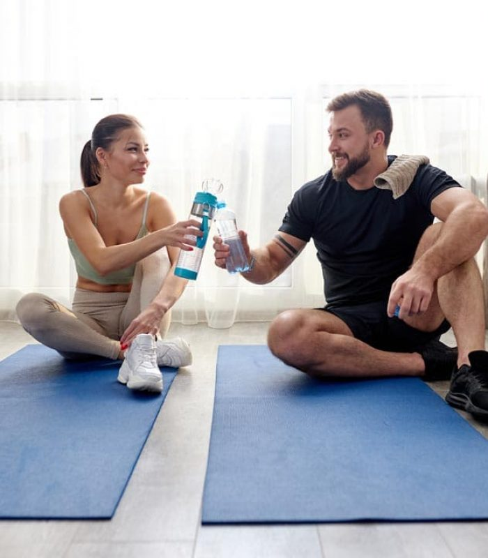 caucasian sportive couple after training workout at home, take a break sitting on fitness mat